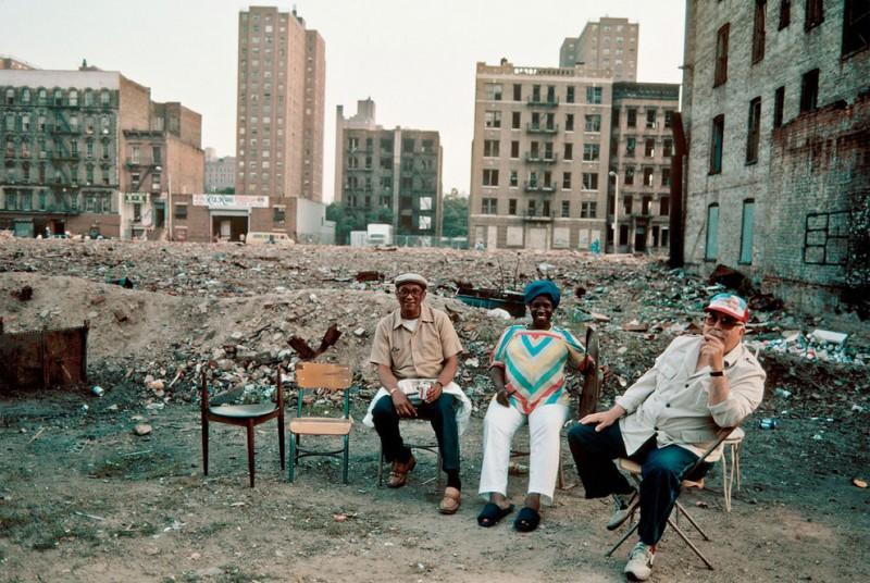 Жители на фоне разрушенных построек