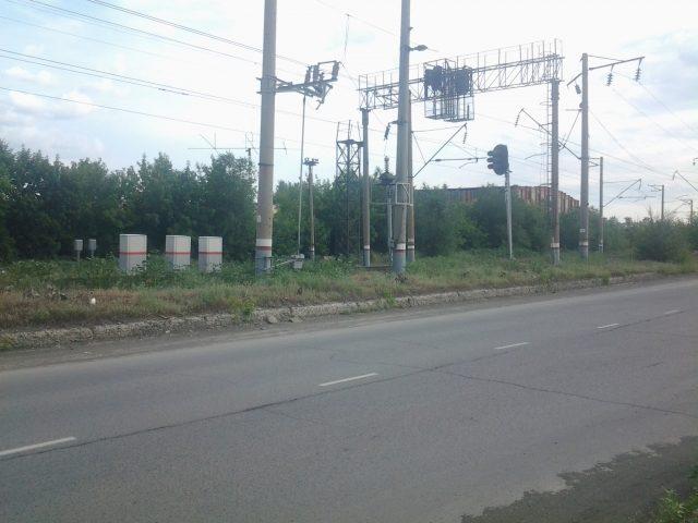 Железнодорожные пути возле автомобильной дороги, справа от дороги - забор завода